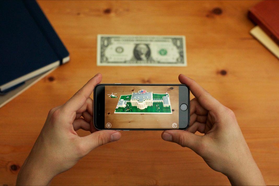 ہاتھ میں تھامے ہوئے فون کی سکرین پر وائٹ ہاؤس اور میز پر رکھا ہوا ڈالر کا نوٹ دکھائی دے رہا ہے۔ (White House)