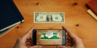 Hands holding a phone displaying the White House and dollar bill on the table (White House)
