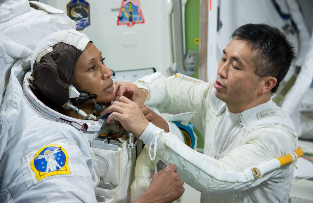 Koichi Wakata (right) helping Jeanette Epps fasten something on space suit (NASA)