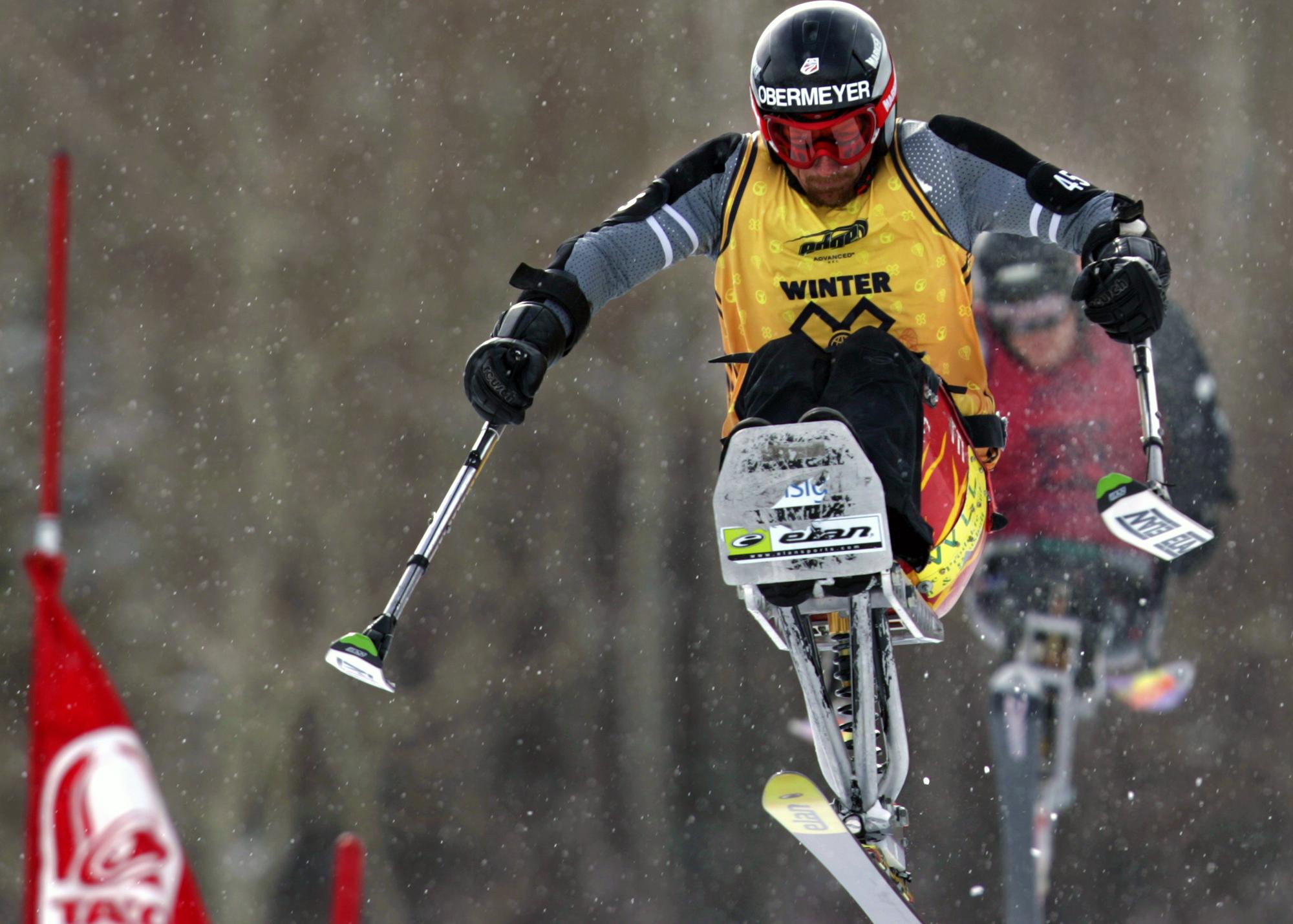 Skiier in air on mono-ski (© AP Images)