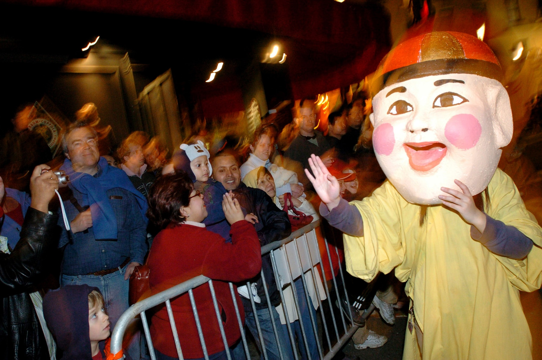 Performer in large face mask waving to crowd behind barricade on street (© AP Images)