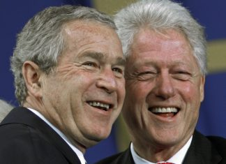 Close-up of George W. Bush and Bill Clinton smiling (© AP Images)