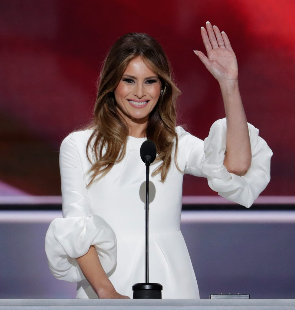 Woman in white dress waving hand (© AP Images)