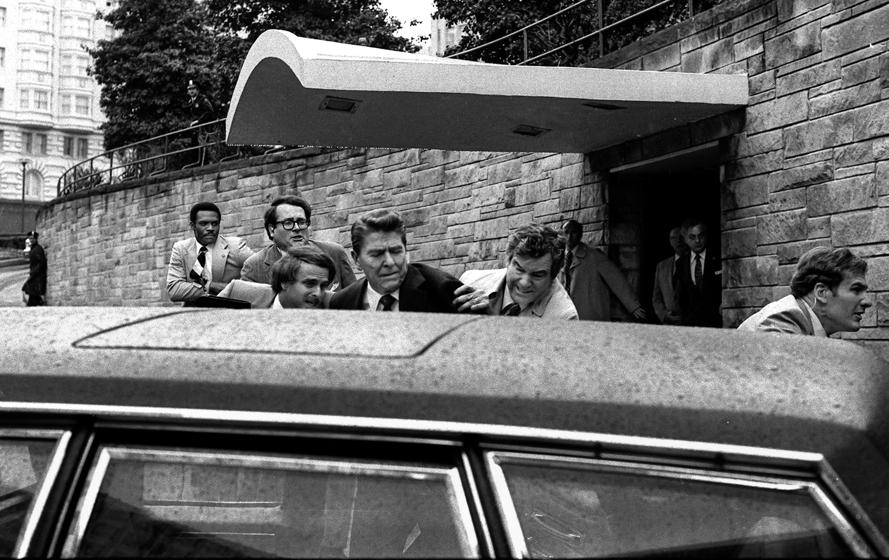 Men directing Ronald Reagan into car (© AP Images)