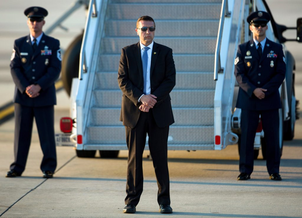 Secret Service and two military personnel standing next to airplane stairs at airport (© AP Images)