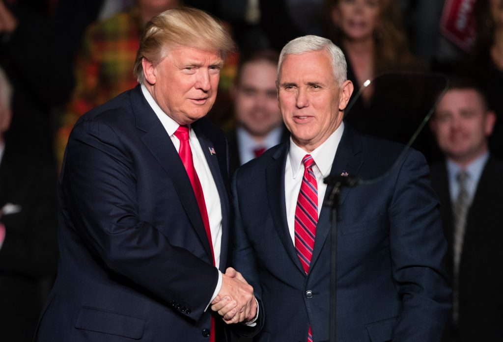 Donald Trump shaking hands with Mike Pence (© AP Images)