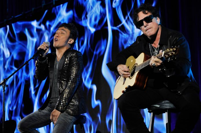 One man singing, another playing guitar (© AP Images)
