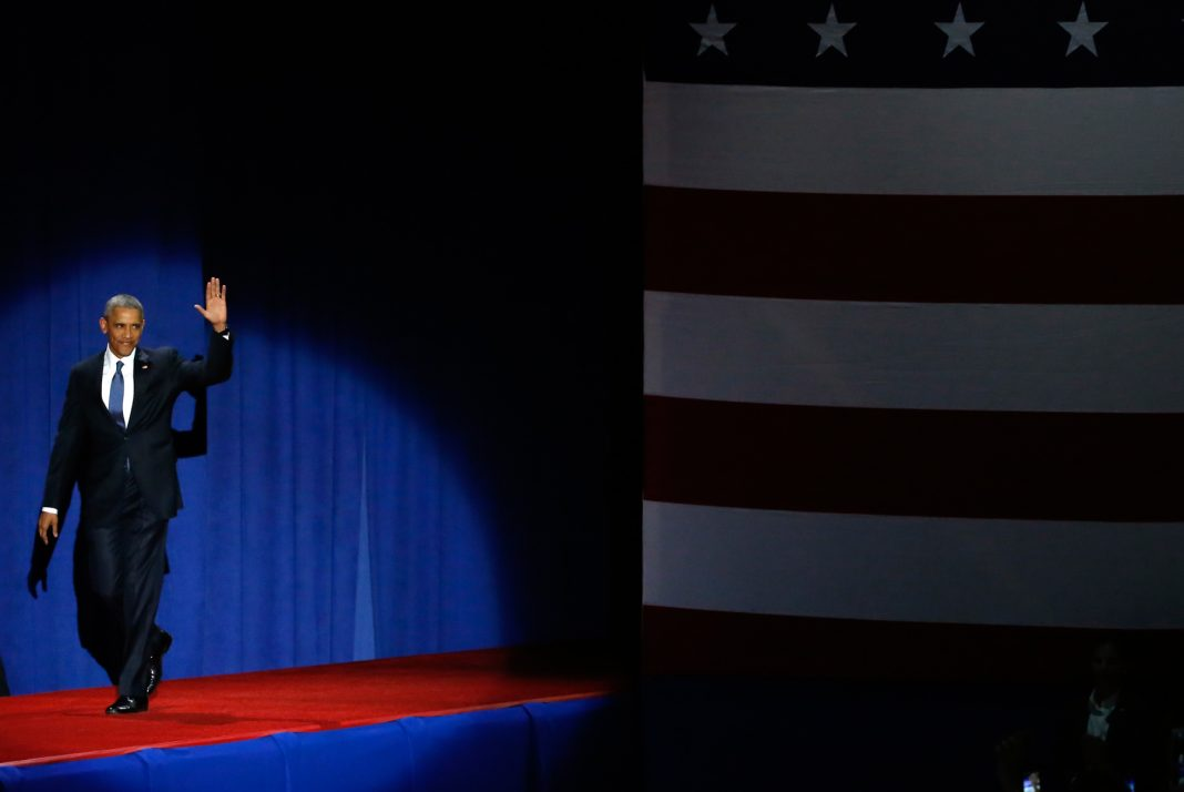 President Obama onstage, waving to crowd (© AP Images)