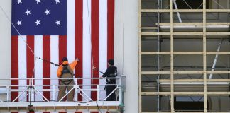 Workers on scaffolding erecting large flag (© AP Images)
