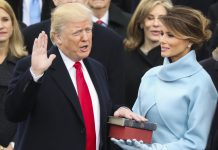 President Trump with one hand raised and one on bible being held by Melania Trump (© AP Images)