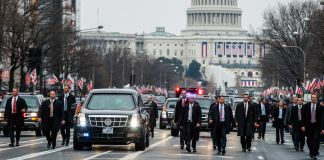 People walking near car on street in front of U.S. Capitol (© AP Images)