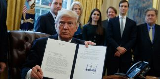 President Trump holding up signed executive order (© AP Images)
