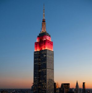 Top of Empire State Building at dusk, lit up in red ( © AP Images)