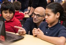 Satya Nadella and two children looking at computer screen (© AP Images)