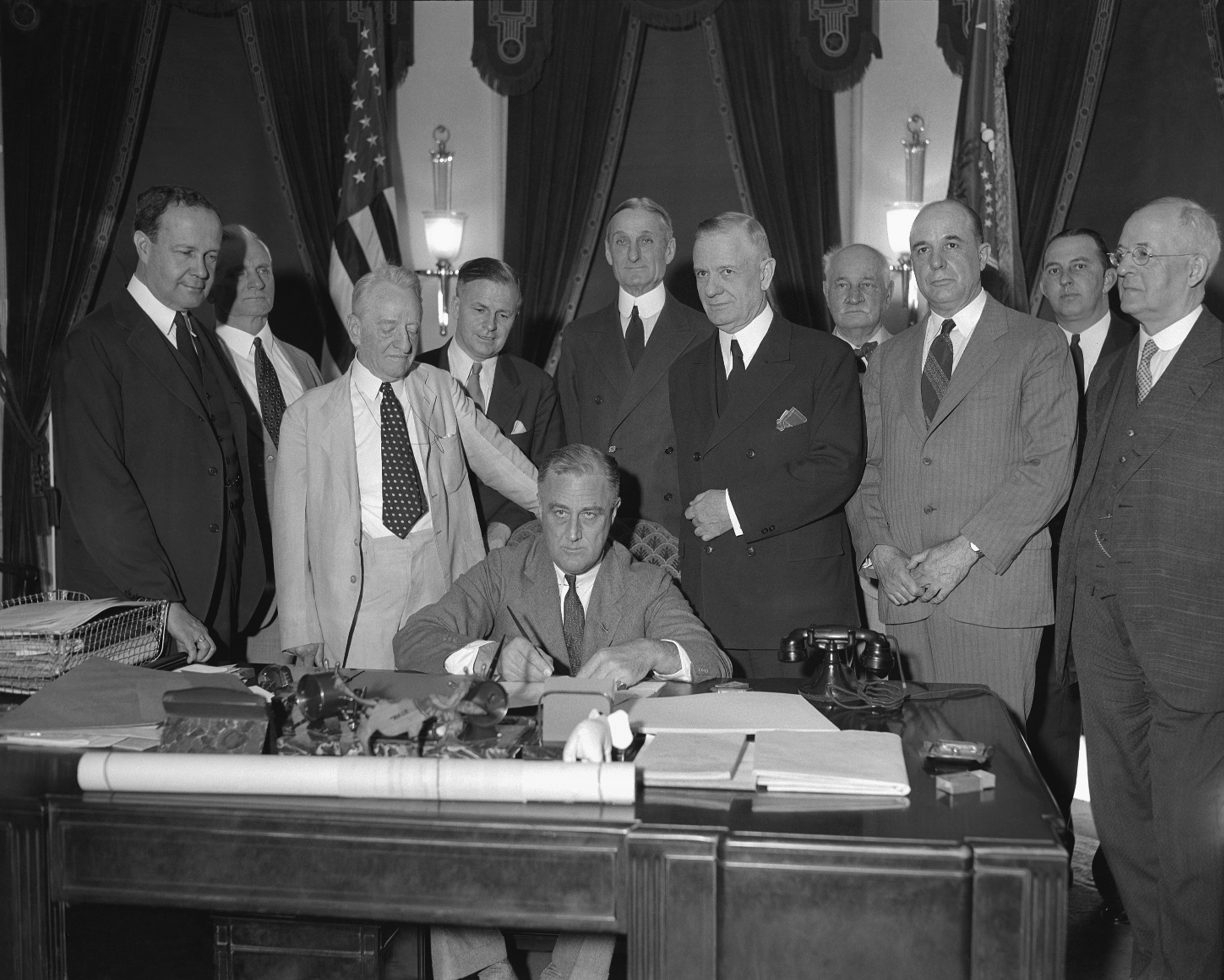 Franklin D. Roosevelt at desk surrounded by men standing (© AP Images)
