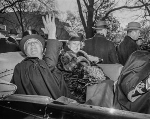 President Franklin Roosevelt waving in car with Eleanor Roosevelt (© AP Images)