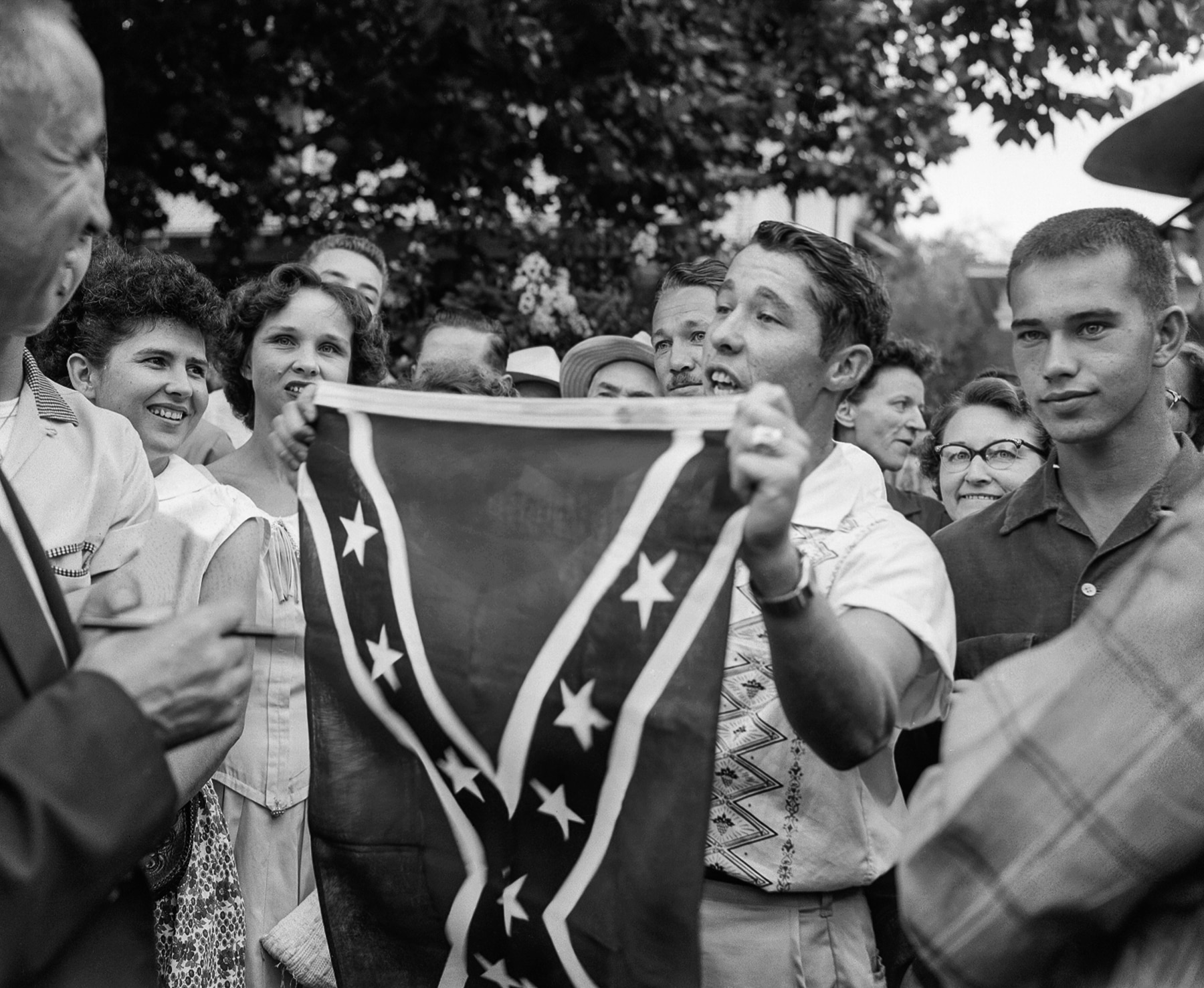 Man in group of people holding flag confronting another man (© AP Images)