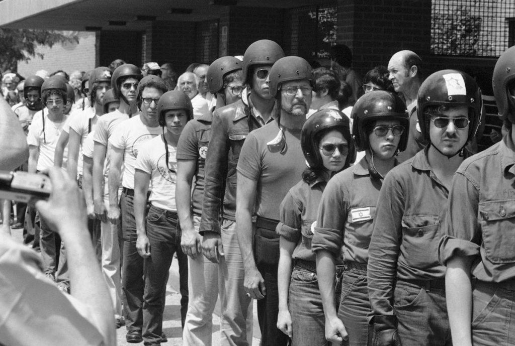Personas con cascos puestos formando una fila (© AP Images)