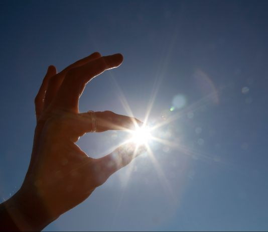 Hand appearing to hold sun between thumb and index finger. (© Design Pics via AP)