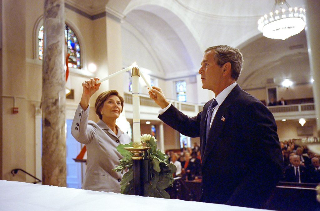 President and Mrs. George W. Bush lighting a candle inside a church (© Eric Draper/AFP/Getty)