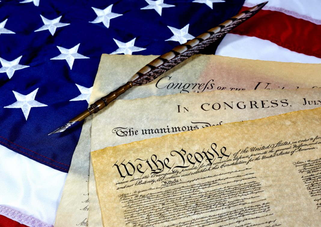 U.S. Constitution with Bill of Rights and Declaration of Independence on an American flag with a quill pen (© Pamela Au/ Alamy Stock Photo)