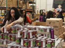 Voluntários manuseiam alimentos enlatados (Corporação para Serviço Nacional e Comunitário)