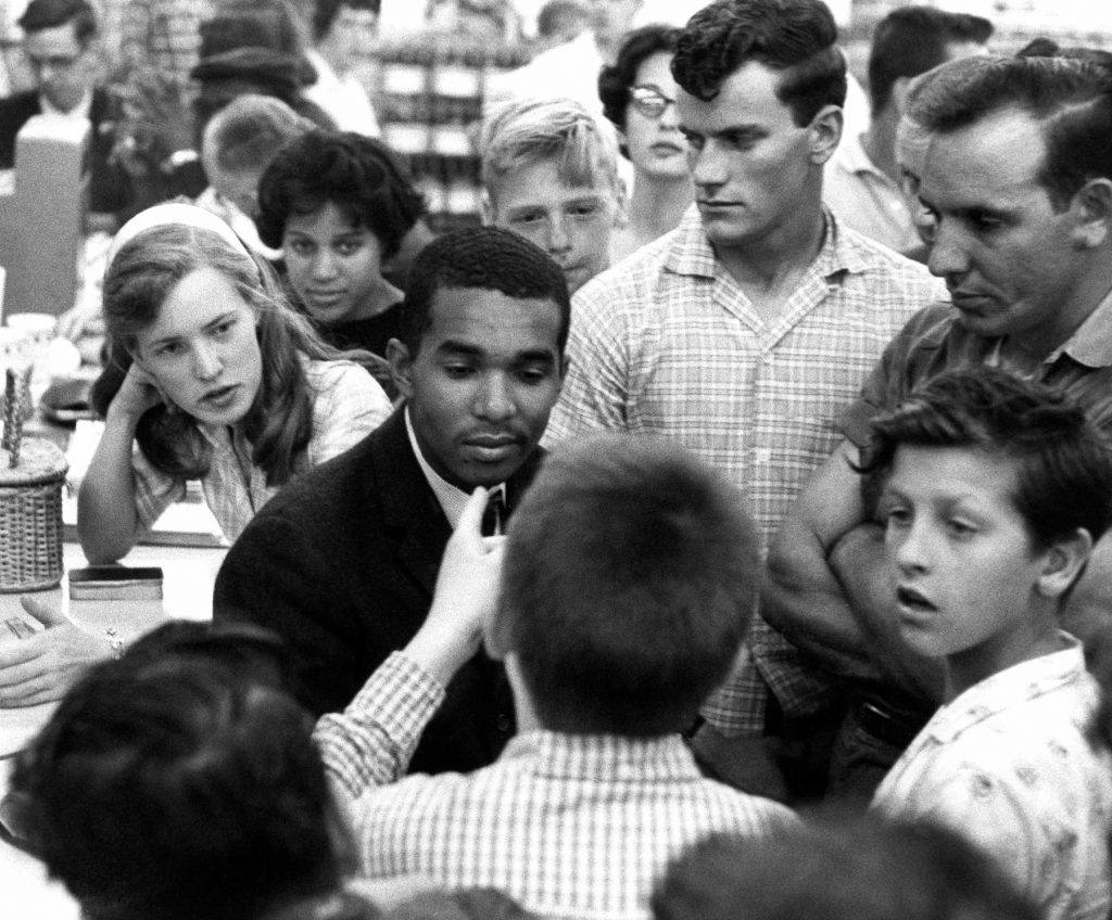 Black and white people in a drugstore (© AP Images)