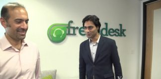 Two people in front of freshdesk logo (VOA)