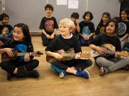 Três crianças sentadas no chão, tocam ukuleles; outras sentadas ao fundo (Cortesia: Academia Khan)