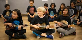 Three children seated on floor, playing ukuleles; other children seated in background (Courtesy of Khan Academy)