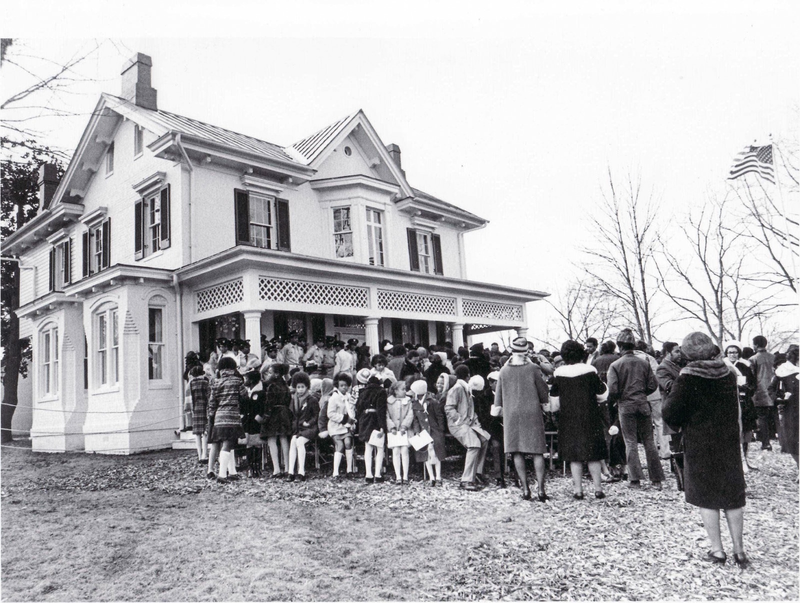 Large two-story house with crowd of people on front porch and in yard (National Park Service)