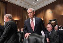 رجل واقف يهم للجلوس في قاعة اجتماعات (© AP Images)