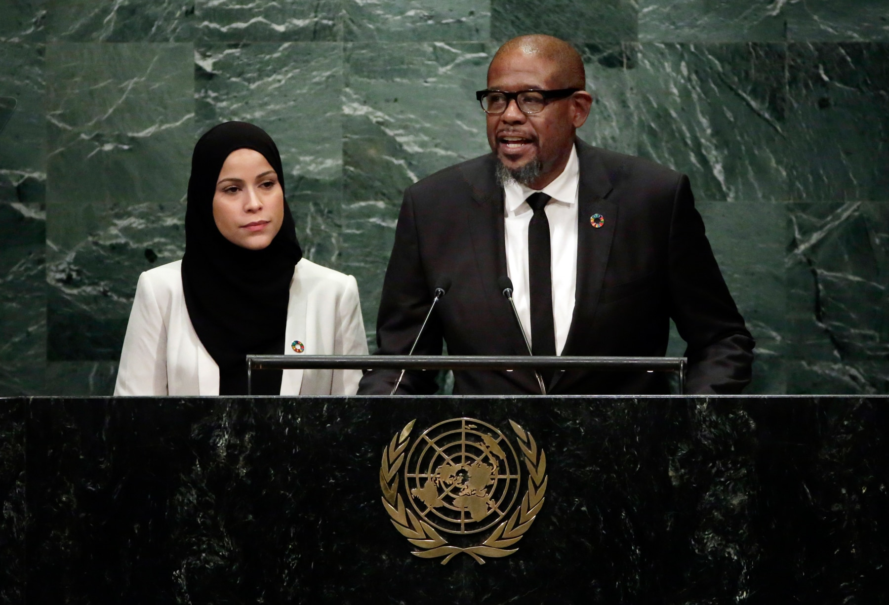 Alaa Murabit standing next to Forest Whitaker at lectern (© AP Images)