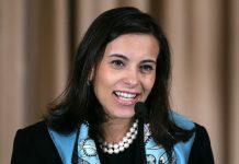 Dina Habib Powell ante un micrófono (© AP Images)