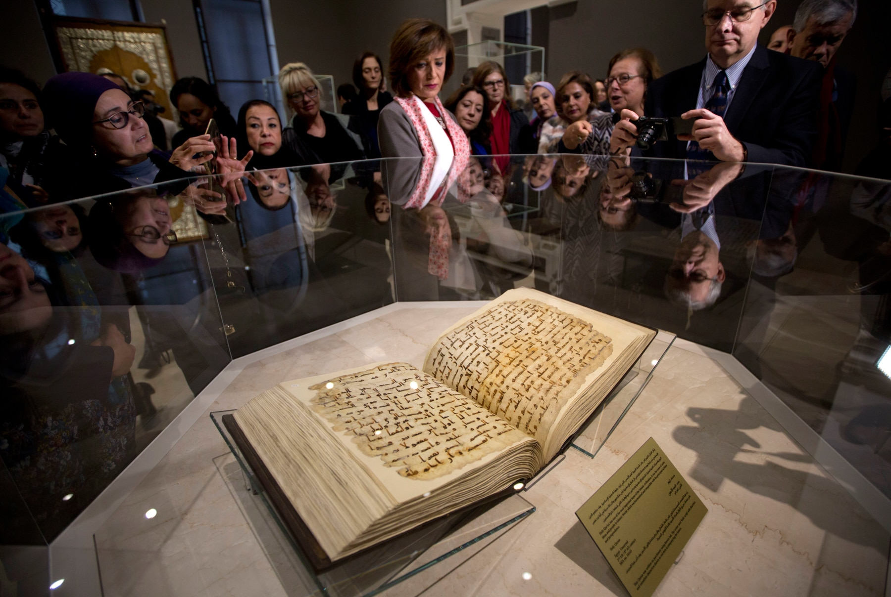 People looking at glass-enclosed book (© AP Images)