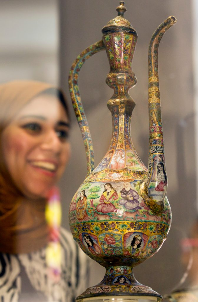 Decorated pot on display, with smiling woman in hijab in background (© AP Images)