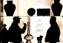 Recipiente de vidro em exposição e silhueta de pessoas atrás (© AP Images)