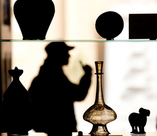 Glass vessel on display, people in silhouette behind it (© AP Images)