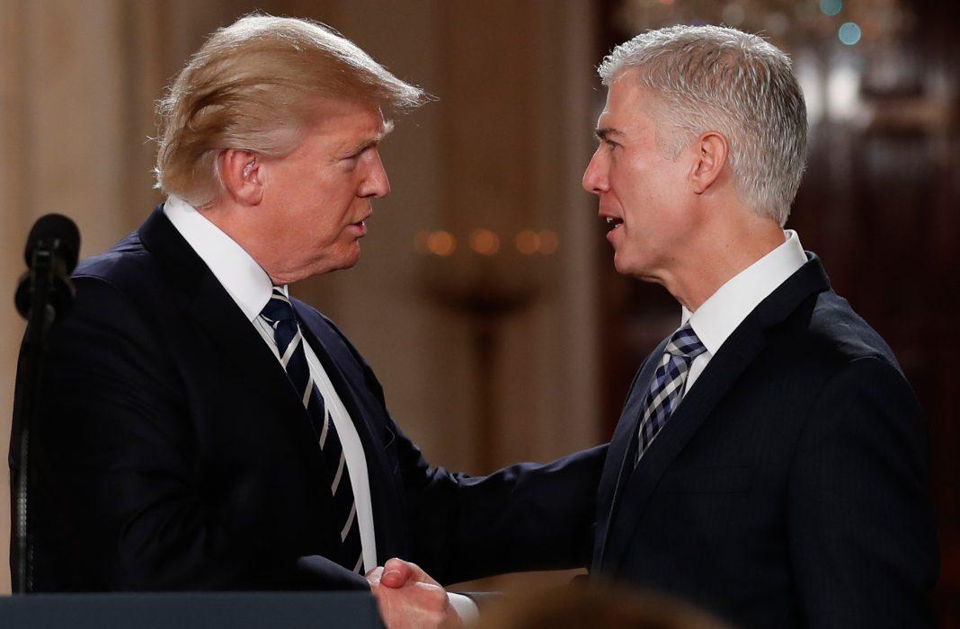 El presidente Trump y Neil Gorsuch se dan la mano (© AP Images)