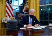 President Joe Biden signing executive orders in the Oval Office (© Evan Vucci/AP Images)