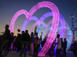 Large, colorful heart shapes with lights and people around (© AP Images)