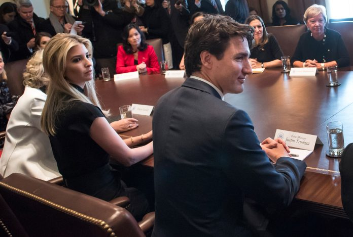 President Trump, Prime Minister Trudeau, Ivanka Trump and others seated around conference table (© AP Images)