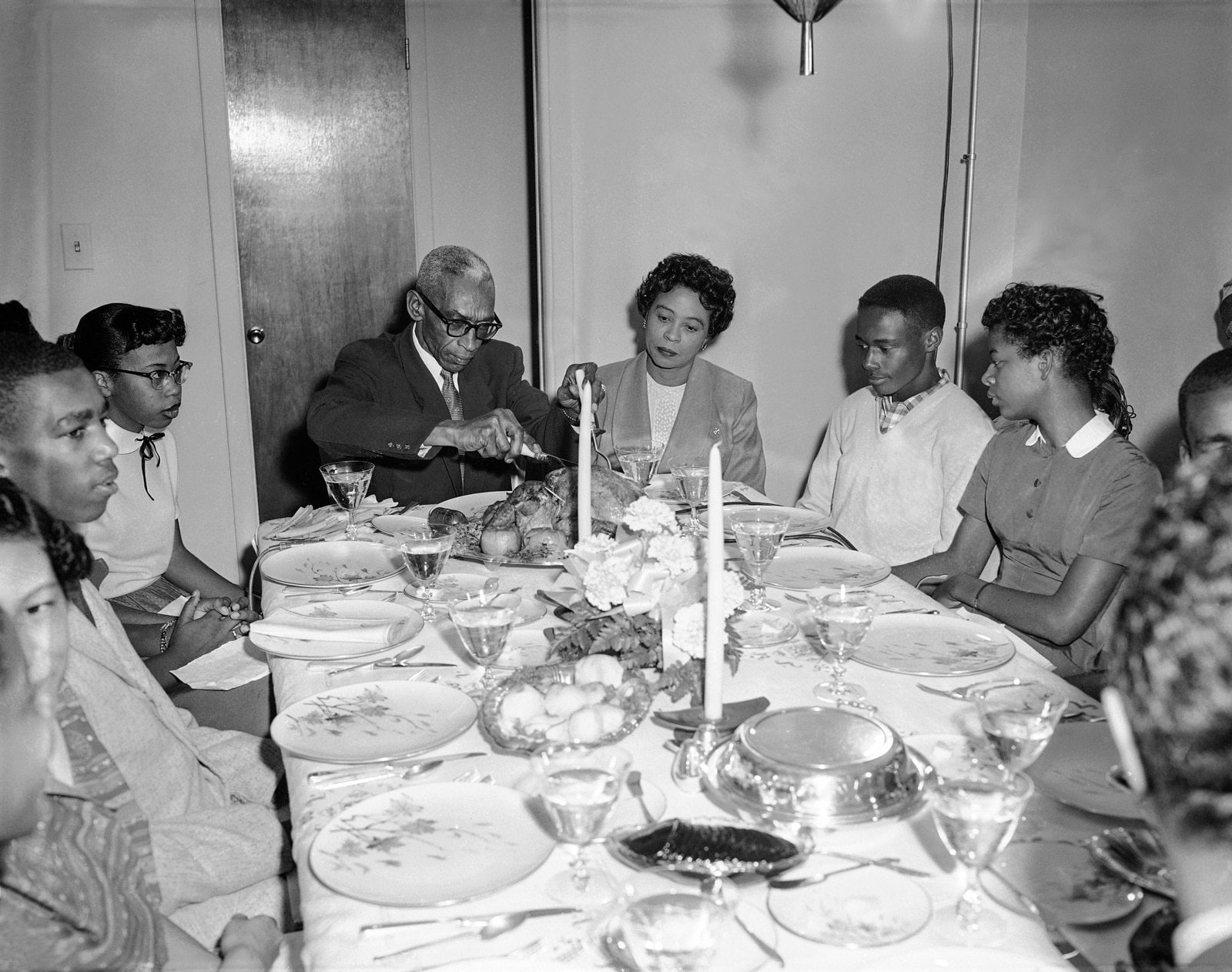 Black-and-white photo of adults and teenagers seated around dinner table (© AP Images)