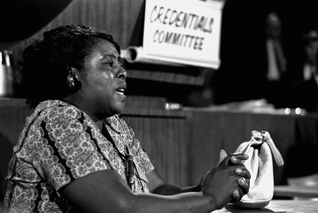Mujer sentada en una mesa con las manos entrelazadas (© AP Images)