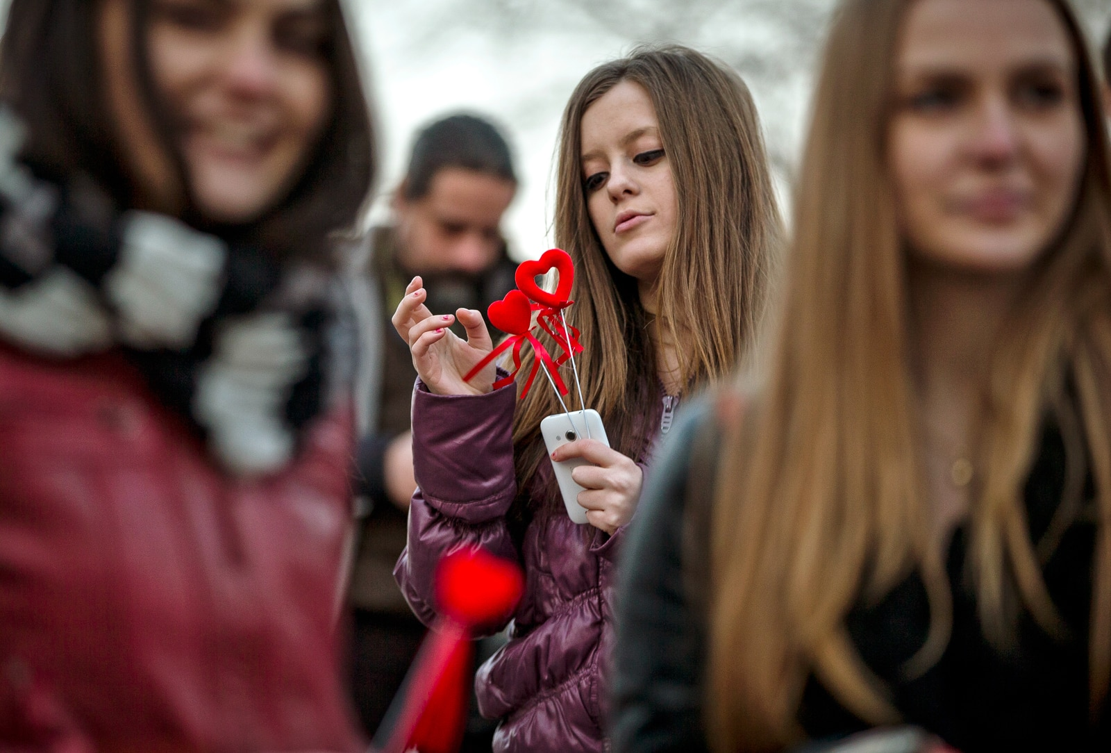 Girl looking at red heart shapes attached to smartphone with people around her (© AP Images)
