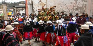 Group of brightly dressed people marching away from camera (© Judy Blankenship/Archivo Cultural de Cañar )