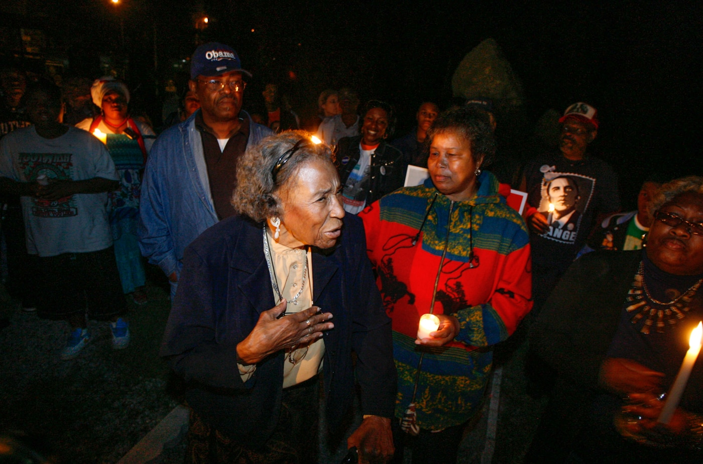 People standing in dark, some holding candles (© Stacey Wescott/Chicago Tribune/MCT via Getty Images)