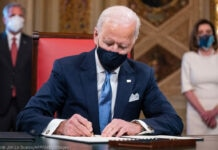 President Joe Biden signing documents in