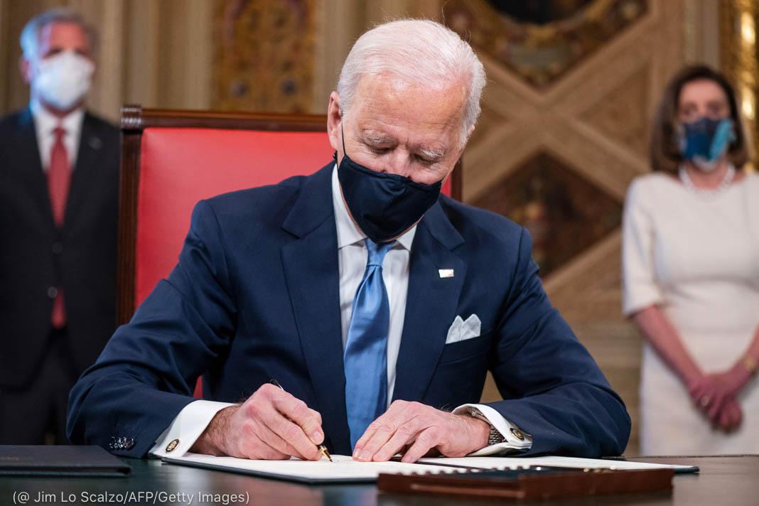 Presidente Biden assinando documentos enquanto duas pessoas observam paradas atrás dele (©Jim Lo Scalzo/AFP/Getty Images)