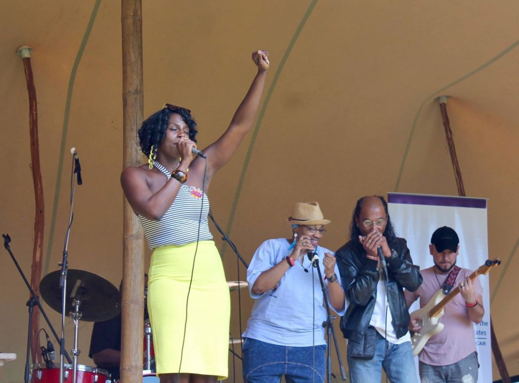 Mahogany Jones with upraised fist and microphone, on stage with three others (Courtesy of Mahogany Jones)